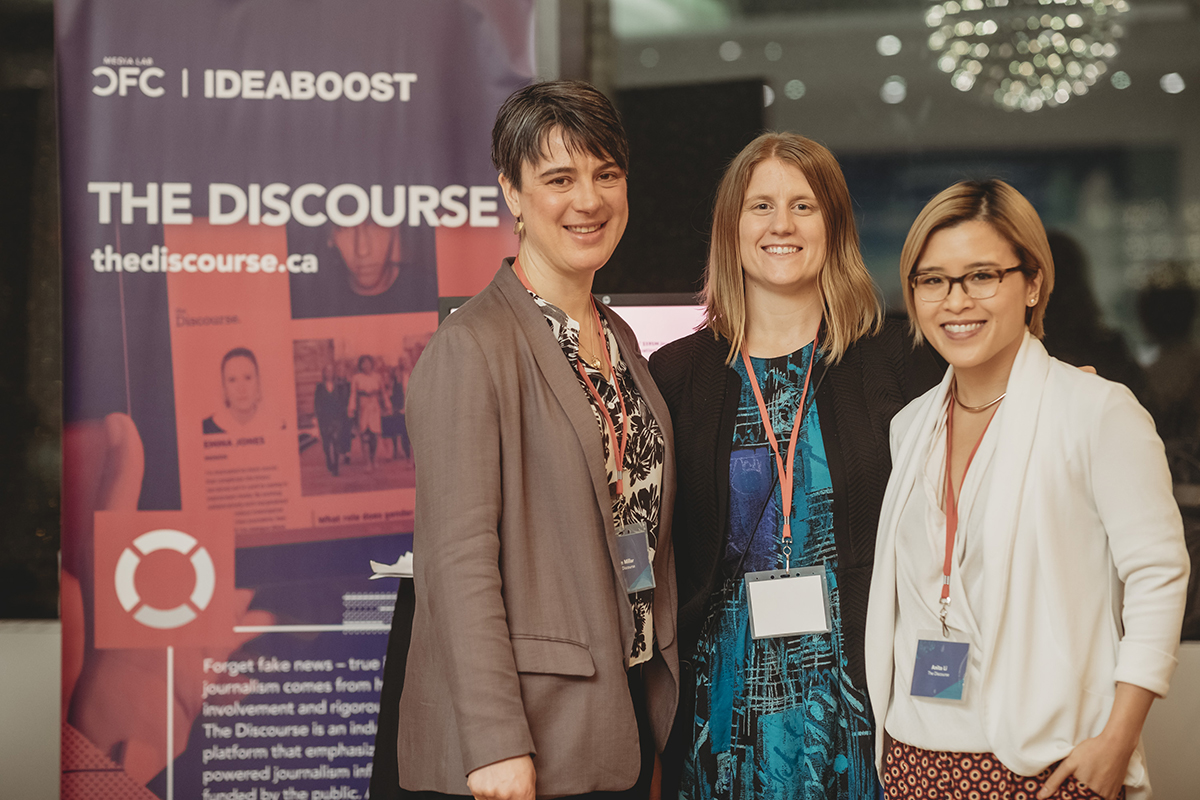 Three women standing next to a pink pull up banner for 'The Discourse'.