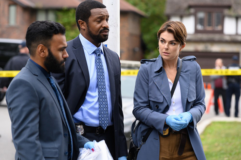 Three people stand together deep in conversation at the centre of a crime scene
