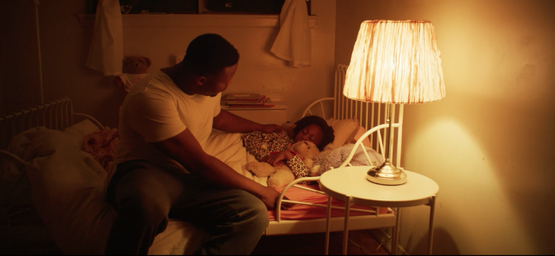 A father tucks his daughter into bed