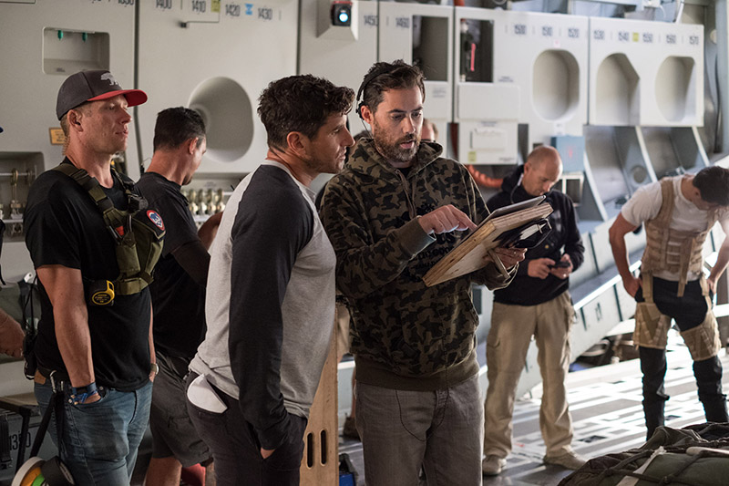 A film director looks down and points to a piece of paper and speaks to another individual on set