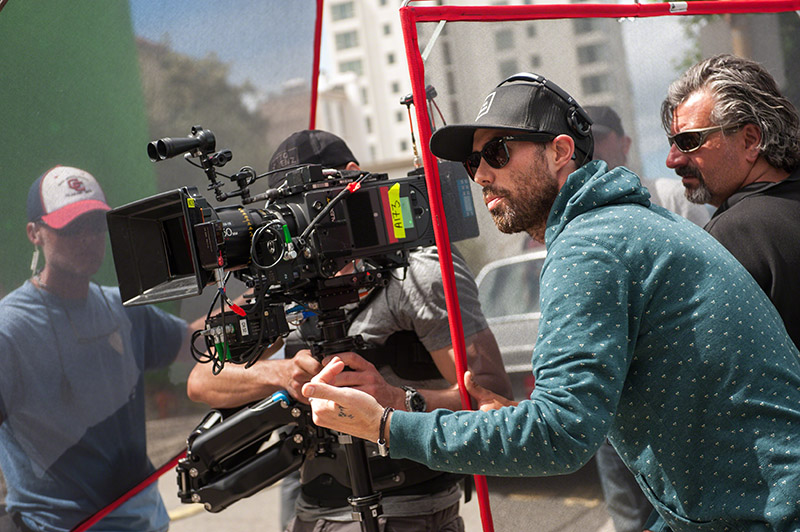 A film director standing beside a camera giving direction on set