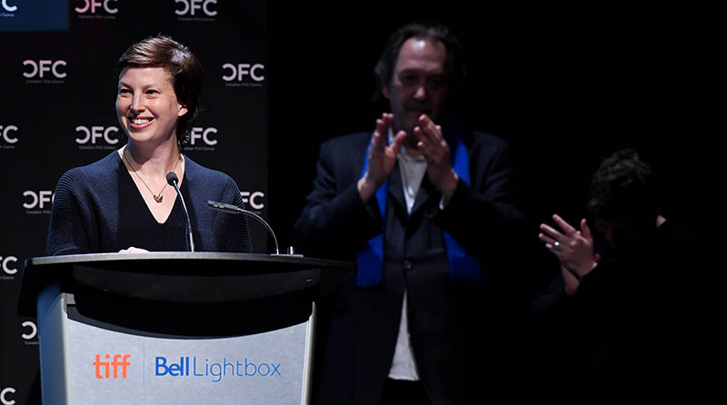 A woman stands at a podium smiling, two people in the behind her stand, clapping