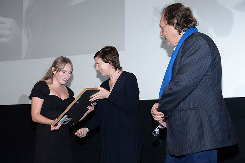 A young woman on stage accepting an award from two individuals.