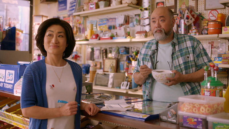 A man stands behind a counter at a convenience store, eating a bowl of cereal, and a woman stands in front of the counter