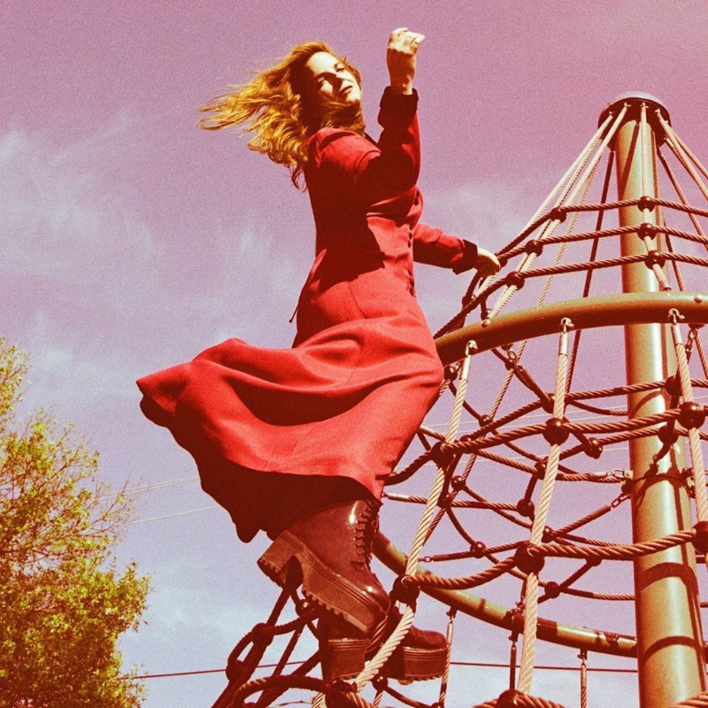 A woman in a red dress poses at the top of a rope climbing structure