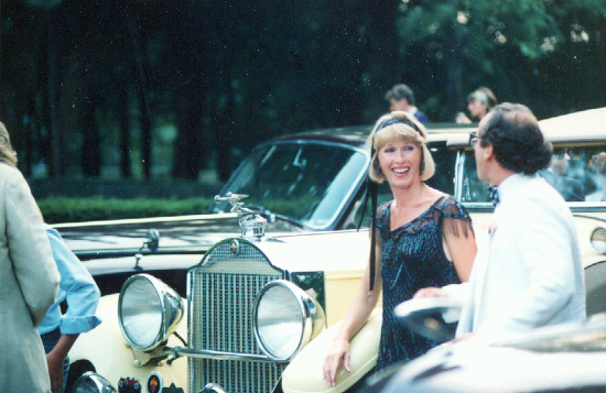 Partygoers dressed in 1920s costumes stand among vintage cars