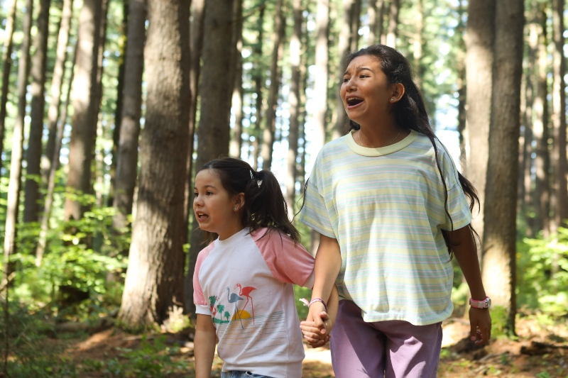 Two young girls hold hands while looking distressed in a forest surrounded by large trees