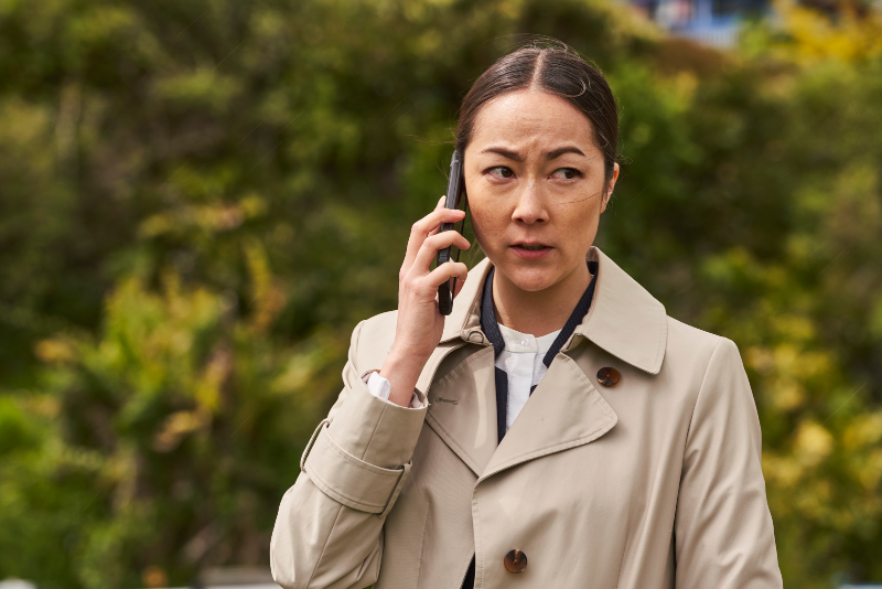 A woman in a trench coat looks off to the side while holding a cell phone up to her ear