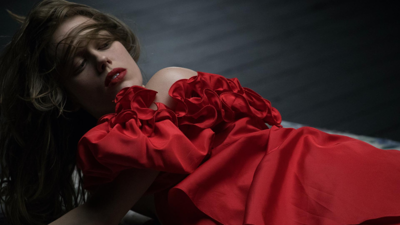 A woman wearing a red dress and red lipstick lies down and looks back