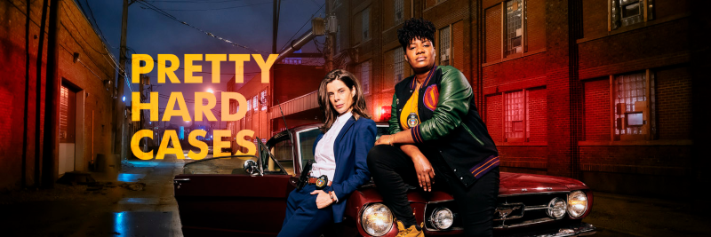 Two female detectives, one leaning against the hood of a car and one sitting on the hood of a car, posing for a promotional picture for a tv series