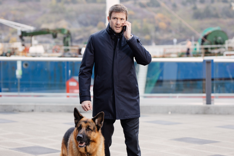 A man walks while holding and talking on his cell phone, his german shepherd walks him