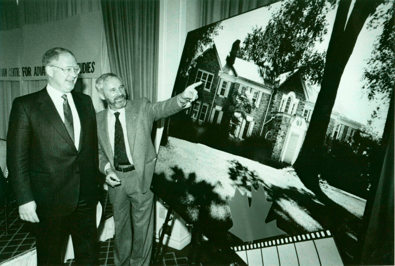 An old black and white image where two men stand side-by-side, one man points to a large image of a house that is displayed on an easel.