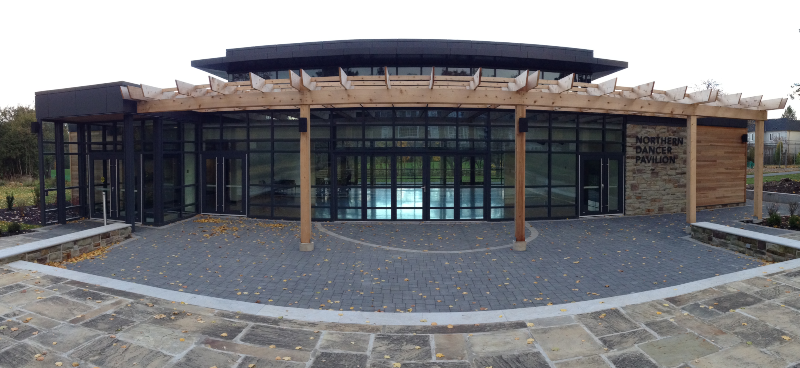 A large modern building with a wooden pergola in the front, and a stone terrace.