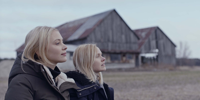 Two sisters look off into the distance, while standing beside each other on a grass field in front of an old barn