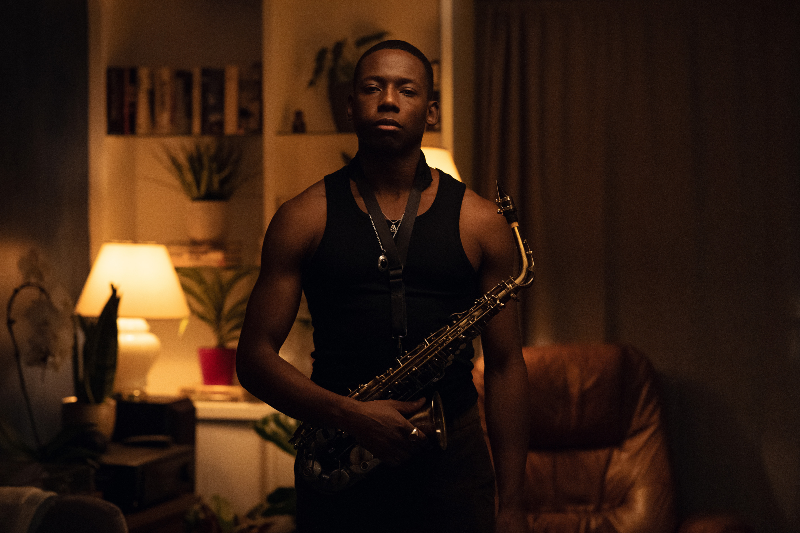 A man standing up holding a saxophone in a dimly lit room