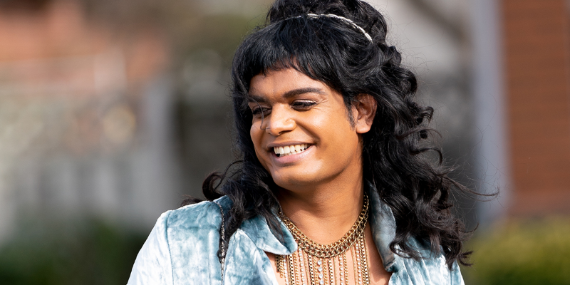 A gender-fluid individual smiles and looks to the left