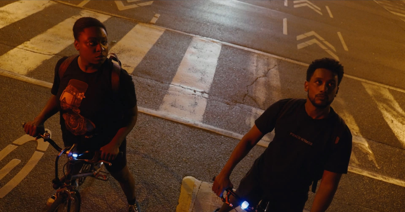Two people stand on their bicycles in the middle of the streets, looking up