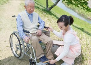 Asian older man man wheelchair with young woman in front of him