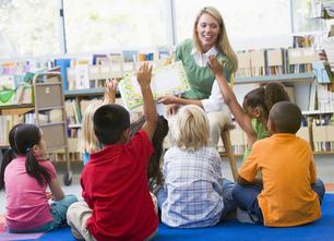 Photodune 313933 kindergarten teacher reading to children in library m