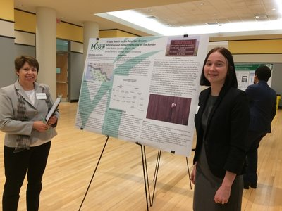 Associate dean, Michele Schweitz, poses alongside global affairs major, Kelsie Rohler, and her poster presentation