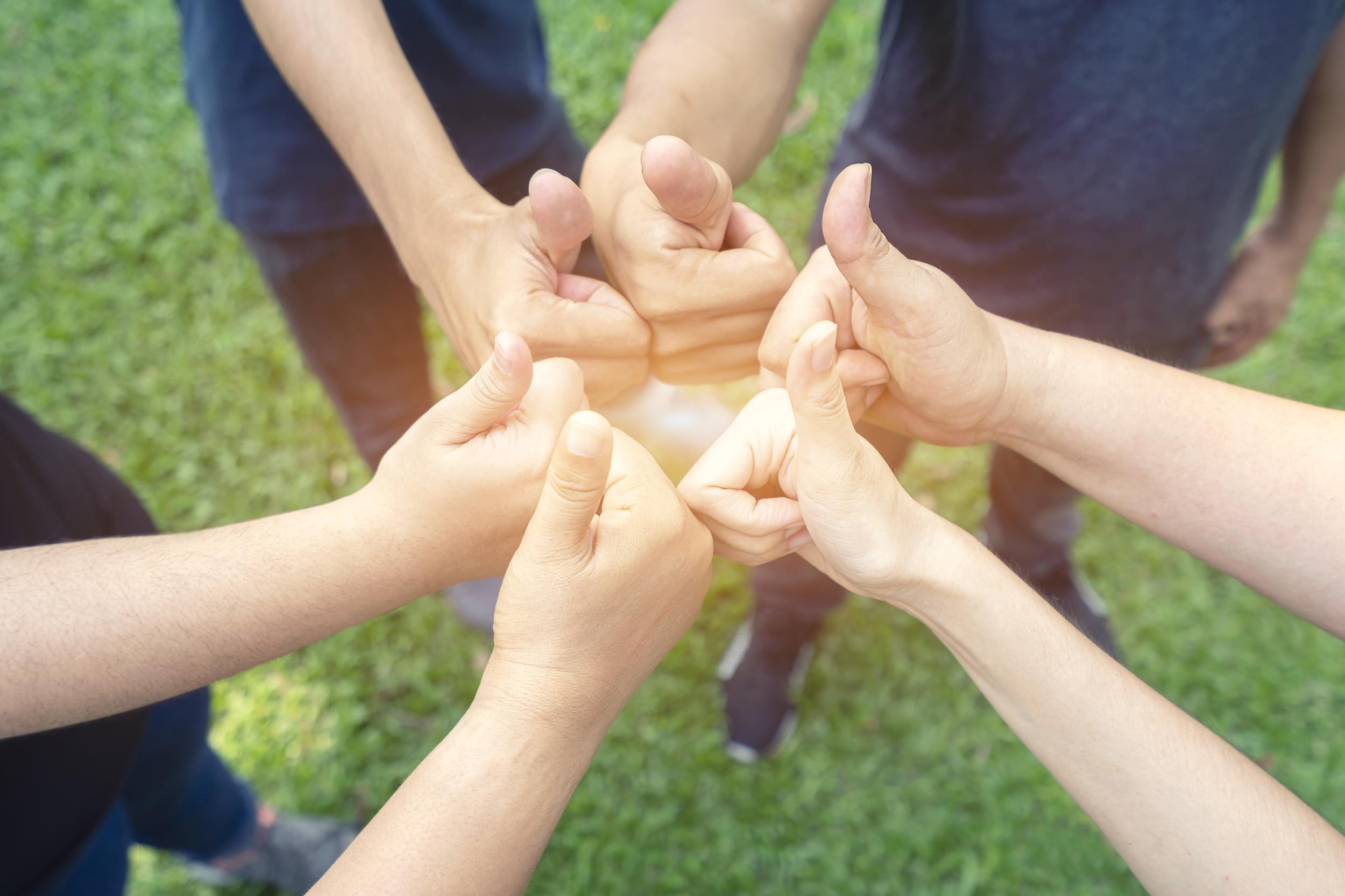 Teamwork togetherness collaboration concept, Group of people giving a thumbs up gesture of approval an success with their hands raised against huddle together, achieve their ultimate goal.
