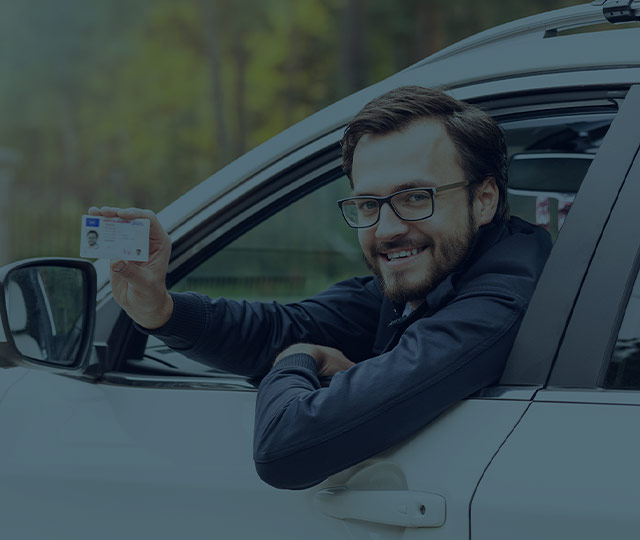 Guy leaning out of vehicle window with a card
