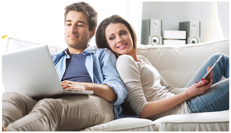 Man and woman on couch looking at a laptop