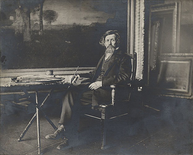George Inness seated in his studio