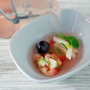 Fruit salad infused broth pouring
