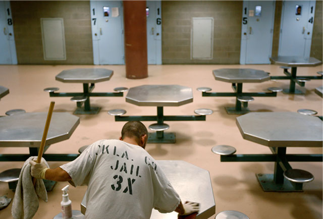 Oklahoma County jail inmate Jesus Lucero cleans an inmate pod along with a group of jail trusties on Tuesday, November 3, 2009
