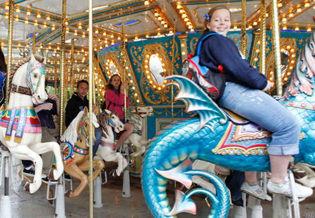 Young people ride on the carousel during the opening day at Frontier City.