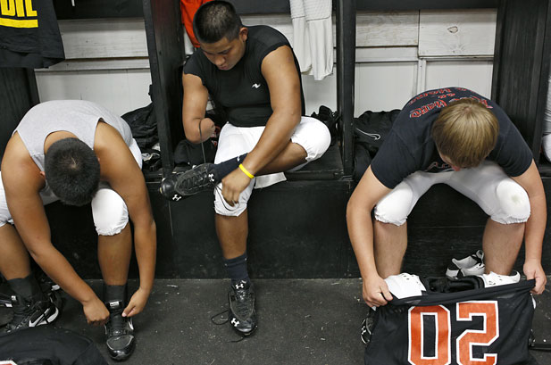 Stephen Cully and his teammates get dressed before practice in the locker room at Konawa High School in Konawa, Okla., on Monday, Aug. 29, 2011.