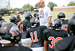 Konawa High School Head Football Coach Brent Damiel talks with his team before practice in Konawa, Okla., on Monday, Aug. 29, 2011.