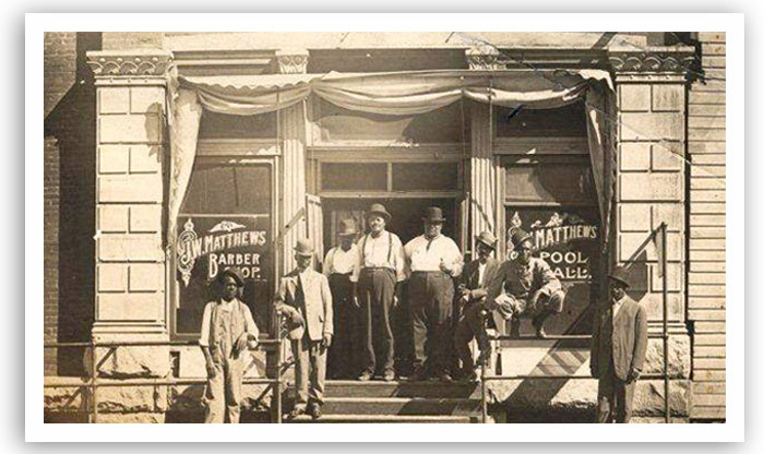 A group of men outside J.W. Matthews' pool hall and barber shop in Guthrie, date unknown.