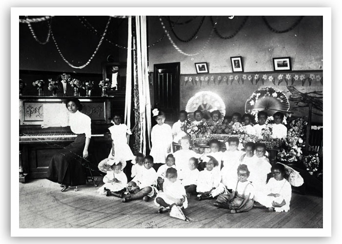 Group of children and their teacher in music class in Guthrie, date unknown. The photo possibly highlights some kind of pageant.