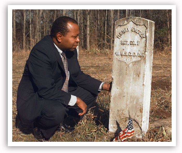 Currie Ballard kneels beside a tombstone in Langston's Beulahland Cemetery in February 1999.