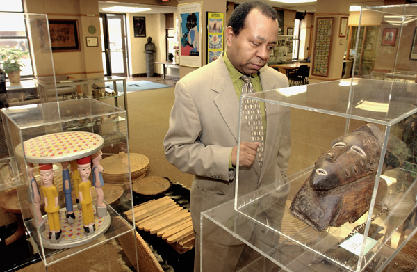 In this 2004 file photo Currie Ballard, who was Historian in Residence at Langston University at the time, looks over a wood mask from Baule, West Africa, which is part of the school's collection.