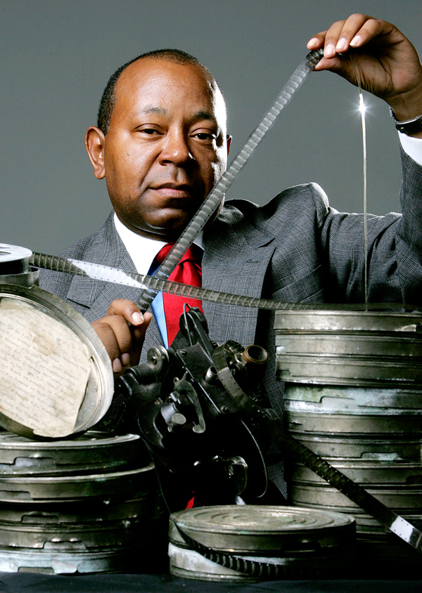 Currie Ballard poses with 29 cans of film he recently purchased from a collector, at The Oklahoman studio in Oklahoma City, Wednesday, Sept. 20, 2006. The films show blacks in the 1920s including a graduation at Langston University, a funeral procession at Hugo, and a cattle ranch at Bristow.