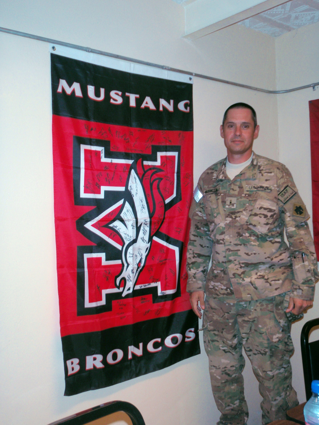 Warrant Officer 2 Todd Warrington stands in front of the Mustang flag his son, Dakaota Warrington sent him. All of the Mustang players signed the flag.