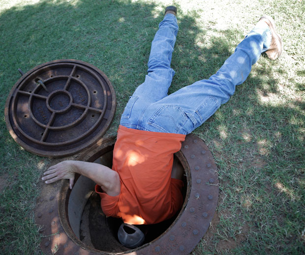 Street superintendent Tenny Maker looks in a manhole in Guthrie.