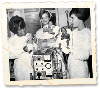 Pictured from left, nurse aide Mrs. Stepney, graduate nurse Mrs. L. Crotty and registered nurse Mrs. N. Schwartz hold infants while standing around the Bourns Pediatric Respirator in 1969.