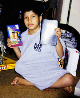 In this undated photo, young Miguel Rayos holds up several books including the Bible.