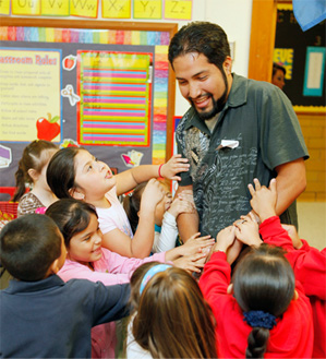 Students at Shidler Elementary clamor for the attention of Miguel Rayos during his recent visit to his alma mater as a volunteer.