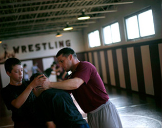 Assistant coach Ronnie Delk instructs a pair of middle school wrestlers during a recent practice. The middle school program has always been important stepping stone and where exceptional talent is identified and developed at an early age
