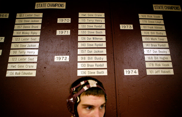 Hayden Workman stands under a list of former Perry champions. Current wrestlers know the school's tradition well and strive to add another layer to it during their careers.