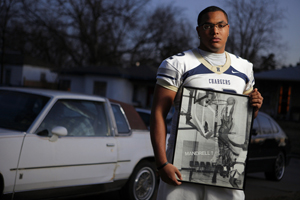 Quintaz Struble holds a photo of his father Mandrell Dean in front of Dean's 1986 Cutlass Supreme, which now belongs to Quintaz. The photo, which hangs on Struble's bedroom wall, shows Dean dunking in a junior high basketball game.