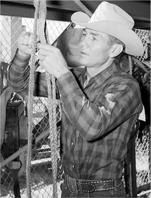 Freckles Brown looks over a bull-riding rope on July 25, 1962, while in Cheyenne, Wyo.