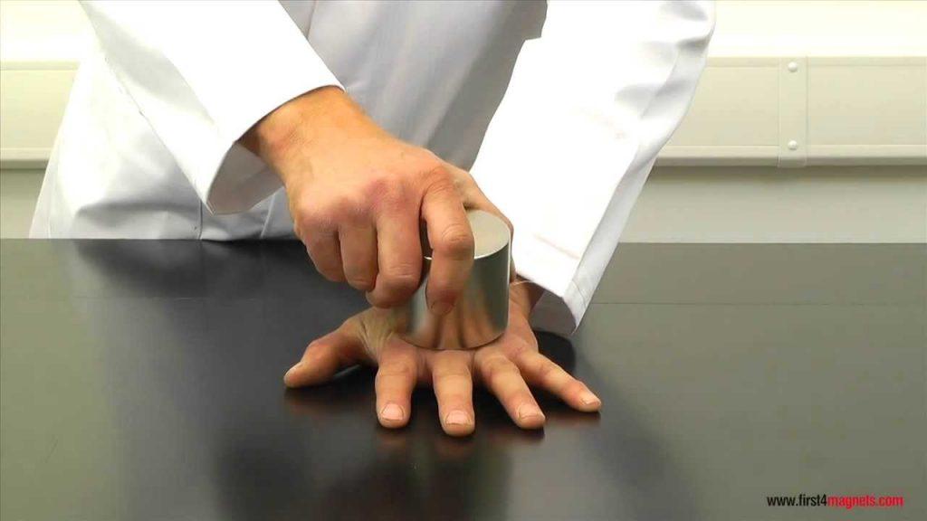 Super-strong neodymium magnets crushing a man's hand