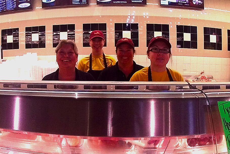 Photo of four deli employees behind hot food case.