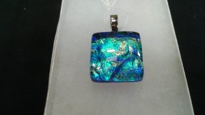 a glass plate and a pendant which is created by Jessica Hockenberry